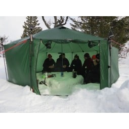 Hilleberg Altai Zelt UL grün im Einsatz mit selbst gegrabenen Schneevertiefungen als Sitzbank